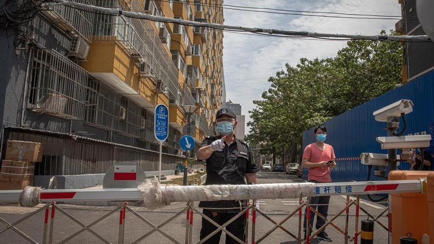 Una persona de seguridad con una mascarilla vigila un complejo residencial cerrado cerca del mercado de Yuquandong, en el distrito de Haidian, Pekín, debido a la propagación de casos de coronavirus.