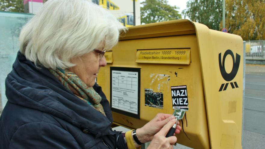 """Irmela Mensah-Schramm raspa una pegatina de un buzón de correos en la que puede leerse """"barrio nazi"""""""
