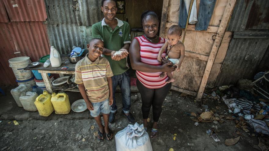 Una familia ante su casa en República Dominicana. Imagen de Pablo Tosco / Oxfam Intermón.