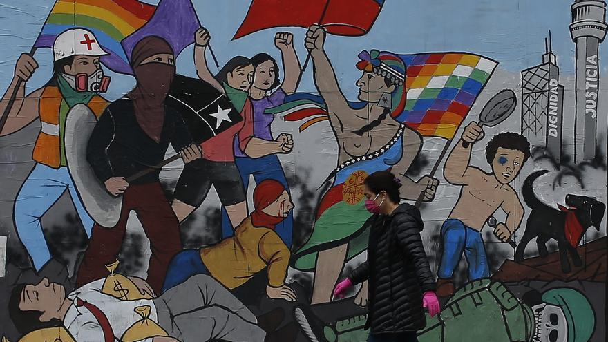 Una mujer con mascarilla y guantes pasa delante de un mural en Santiago de Chile, este 23 de abril