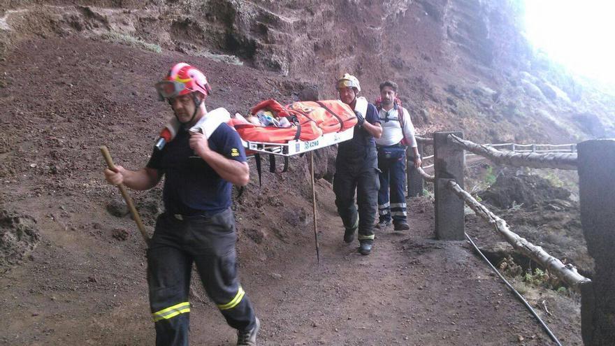 En la imagen, los bomberos trasladan en camilla al bañista rescatado en Nogales. Foto: BOMBEROS LA PALMA.
