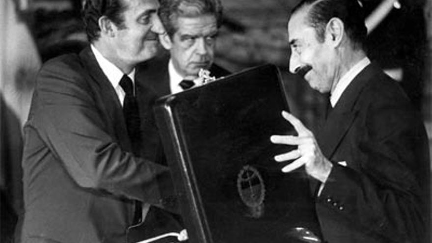 El dictador argentino Videla entrega una placa al rey Juan Carlos