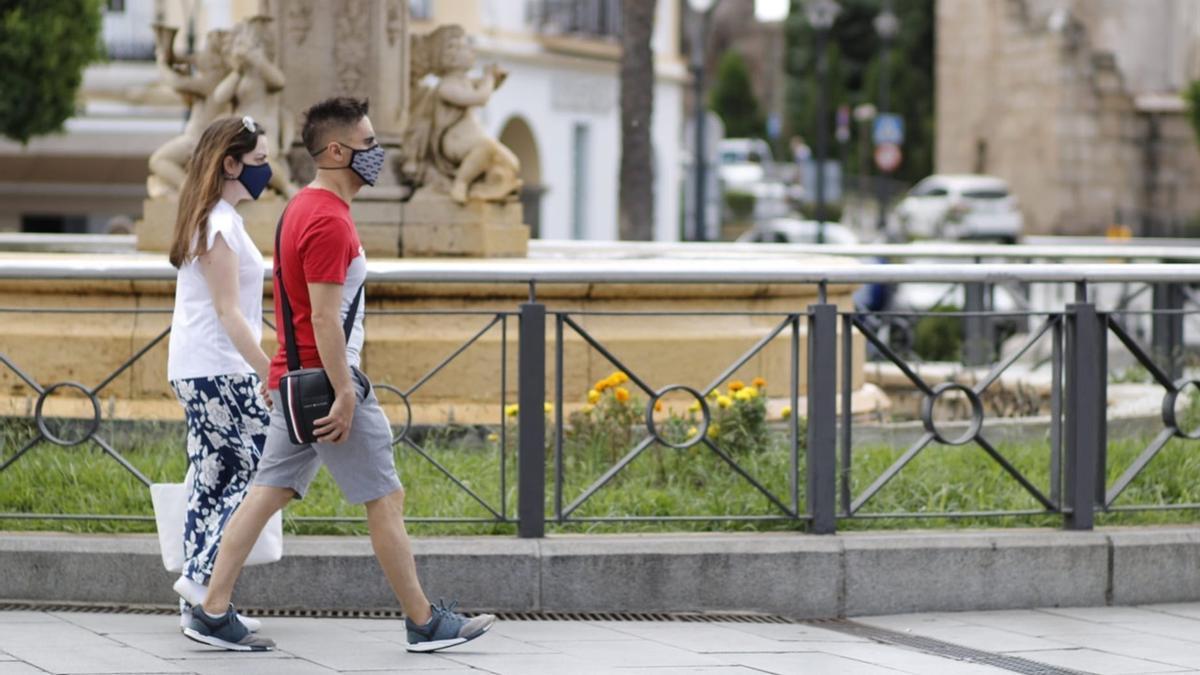 Una pareja con mascarillas pasea por la plaza de España de Mérida