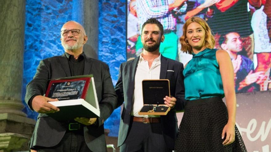 La presidenta del Consejo de la Juventud de Extremadura, Elena Ruiz, hace entrega de las medallas a la Federación Extremeña de Folclore y el grupo Acetre / Junta