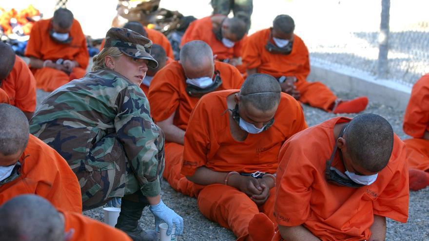 Una policía militar proporciona agua a los detenidos, febrero de 2002 © US DoD