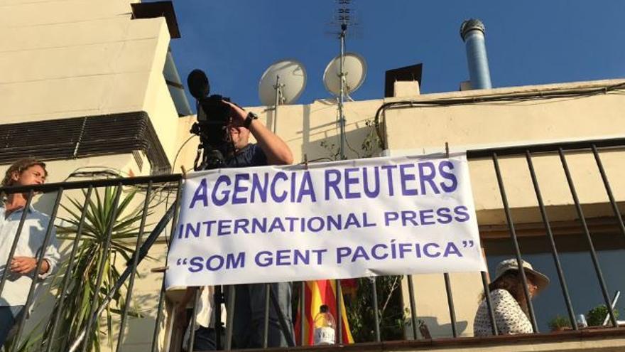 Un cámara de televisión de Reuters en una vivienda de Barcelona con una pancarta para evitar que los acosen durante el referéndum del 1-O.