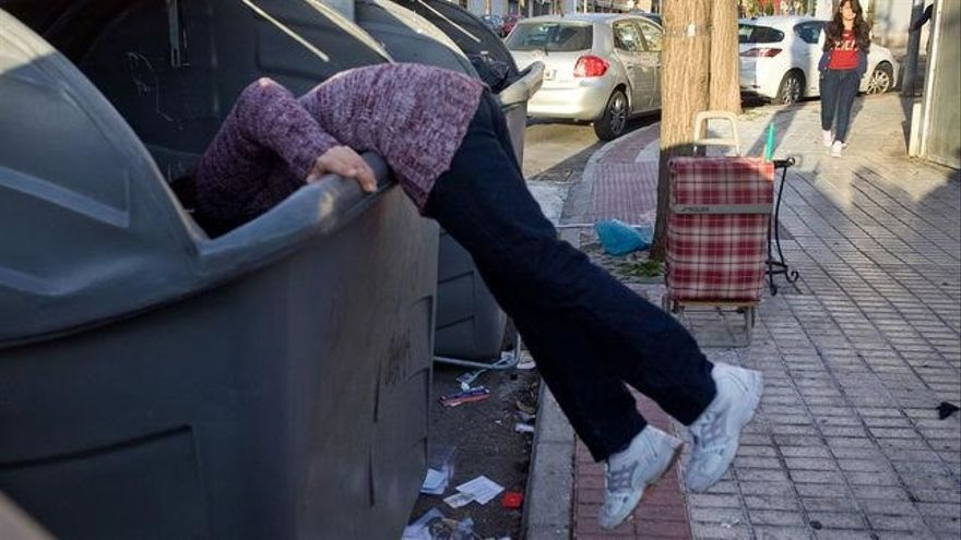 Una persona rebusca en un contenedor.