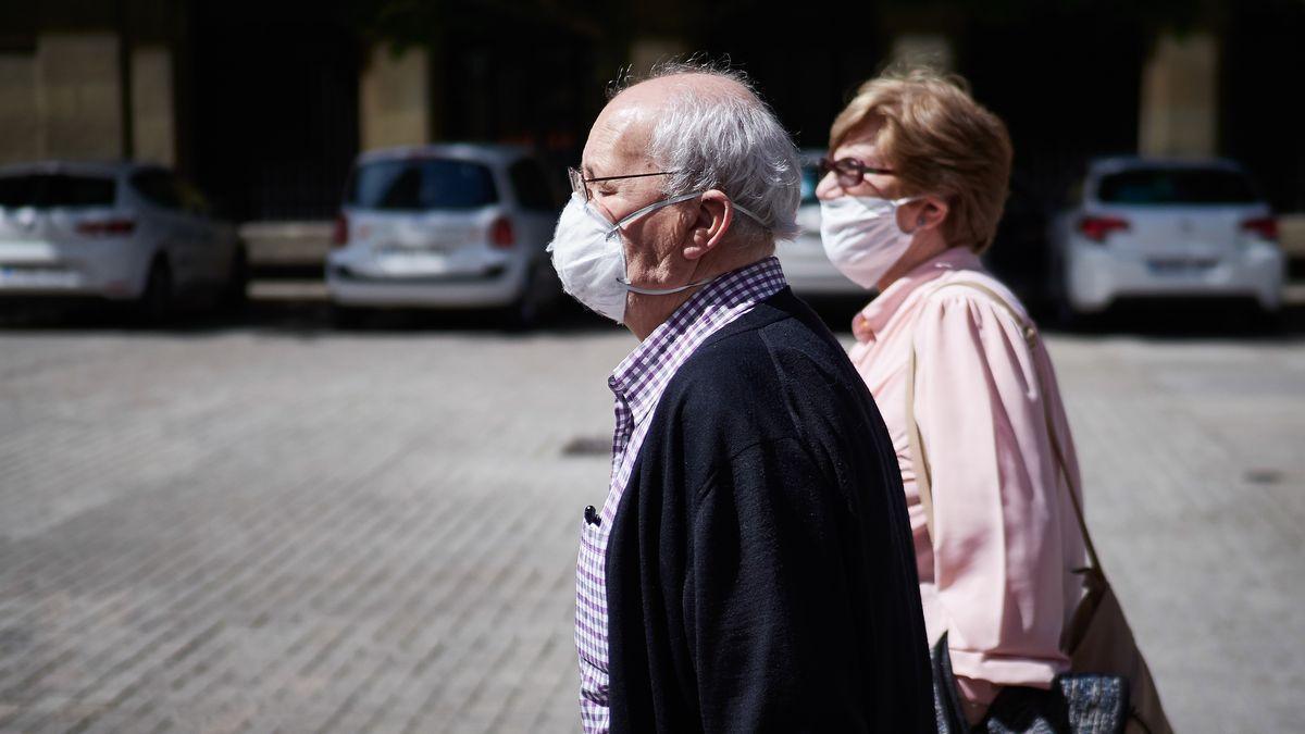 Dos personas mayores pasean por la calle con mascarilla