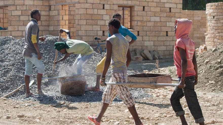 Varios hombres trabajan en la construcción de una calzada.