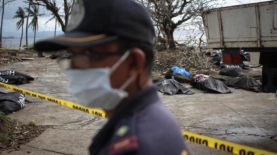 Un policía, en las cercanías del ayuntamiento de Tacloban, ayuda en las tareas de recuperación e identificación de cadáveres, el 14 de noviembre de 2013, Filipinas/ Fotografía: Acción contra el Hambre/Daniel Burgui.