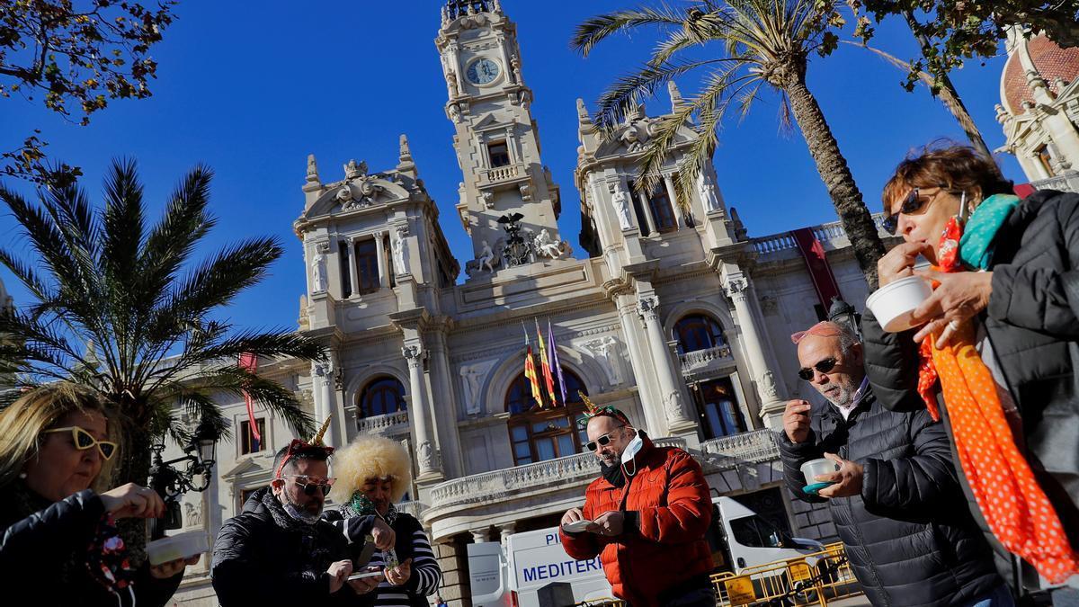 Un grupo de amigos adelanta la Nochevieja, ante las restricciones impuestas por la pandemia, y se han tomado las uvas al sonar las doce del mediodía en el reloj del Ayuntamiento de Valencia. EFE/Manuel Bruque