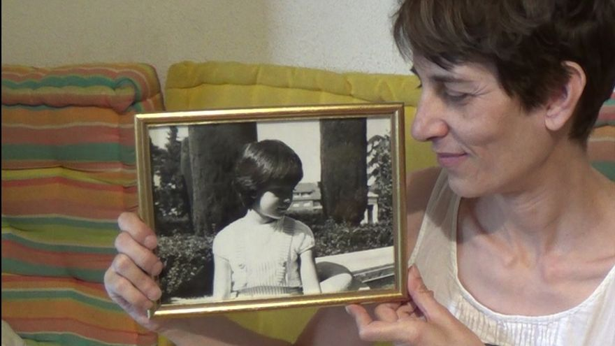 Chus Gutiérrez, parte de la querella argentina, sostiene una foto de ella de niña. / Foto cedida