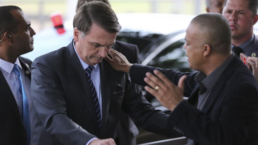 Jair Bolsonaro, orando con un pastor evangélico en la puerta del Palacio de la Alvorada, en Brasília