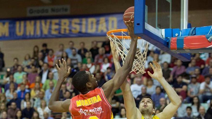 El pívot de UCAM Murcia Moreira (c) hace un mate ante el ala-pívot Gacic de Iberostar Tenerife (d), durante el partido de la jornada trigésimo primera de la Liga Endesa, que ha enfrentado a los dos equipos en el Palacio de Los Deportes de Murcia.EFE/Marcial Guillén