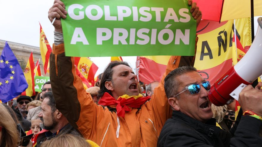 Un manifestante muestra un cartel de 'Golpistas a prisión' en la manifestación de PP, Ciudadanos y Vox en Colón.