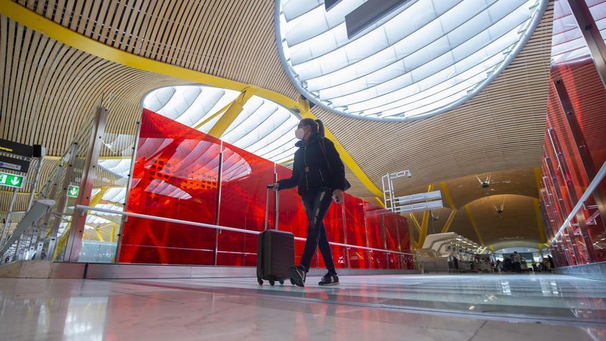 Archivo - Una pasajera desplaza su maleta por las instalaciones de la T4 del Aeropuerto Adolfo Suárez Madrid-Barajas
