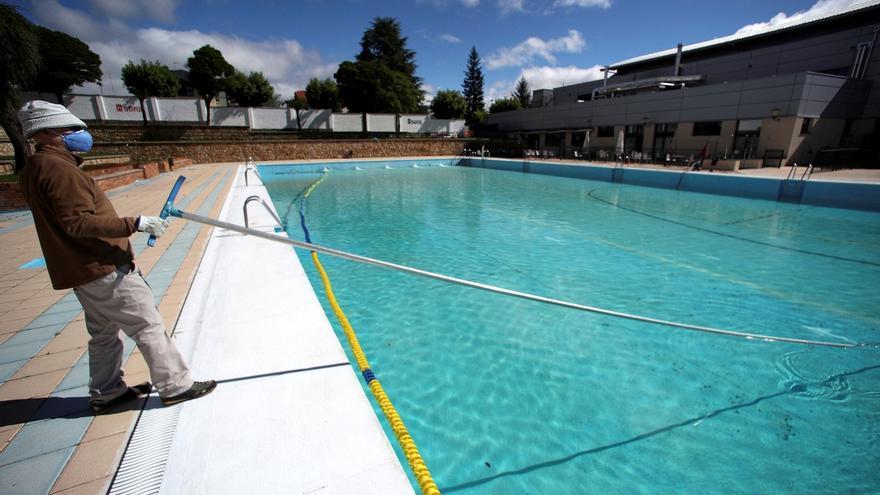 Un operario limpia una piscina.