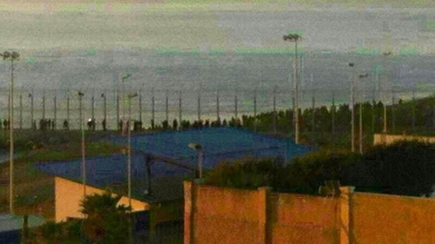 Al fondo, el grupo de personas que ha intentado cruzar la valla de Ceuta