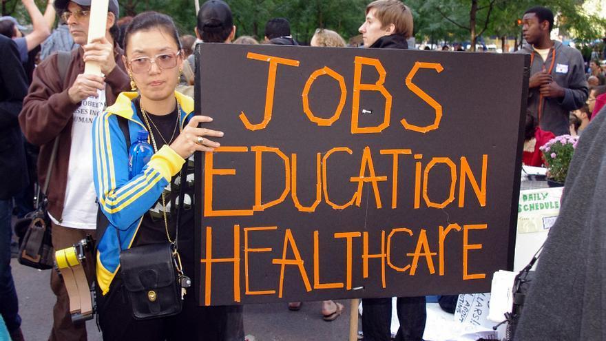 """Manifestación del movimiento Occupy Wall Street, en octubre de 2011. La pancarta dice: """"Empleos, educación, asistencia sanitaria"""""""