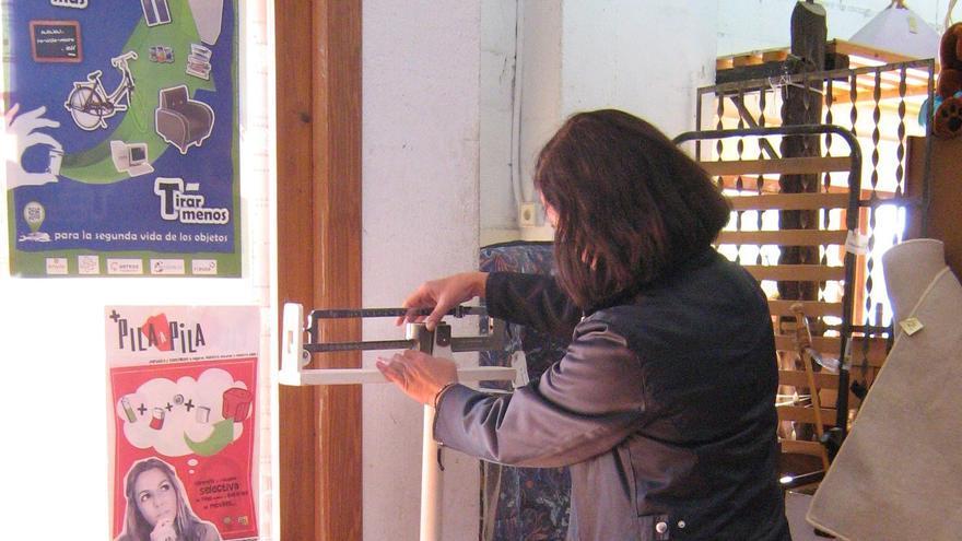 Un mujer pesa un objeto que acaba de comprar en un local de segudna mano. / AERESS