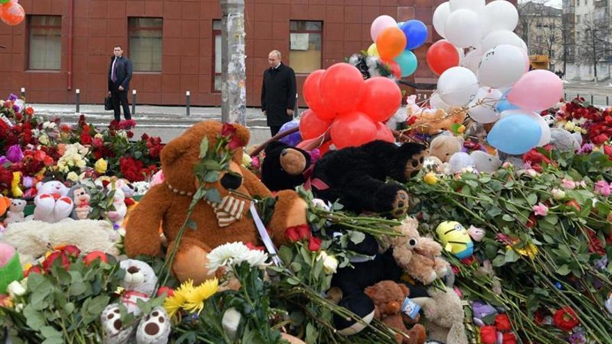 El presidente ruso Vladimir Putin (c) visita un sitio conmemorativo improvisado para las víctimas de un incendio en el centro comercial de Kémerovo