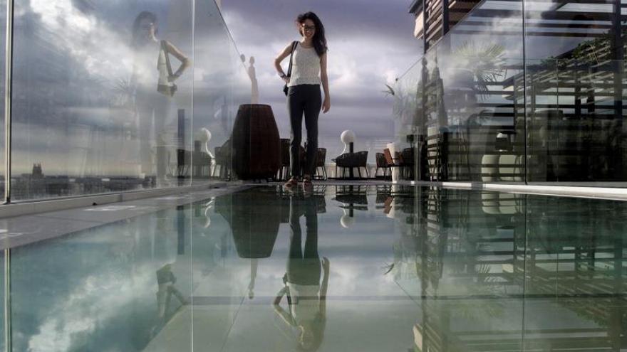 Una joven se dispone a cruzar este martes la pasarela de cristal de la azotea del nuevo Hotel Riu, ubicado en el Edificio España, que se ha convertido en pocos días en uno de los nuevos atractivos de la capital.