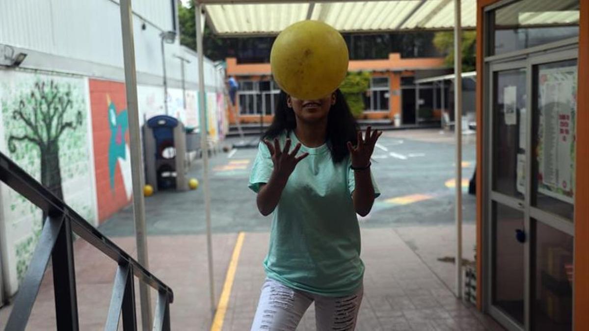 Imagen de archivo. Una niña tira la pelota en el exterior de un centro educativo.