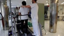 Un paciente que se recupera de un ictus realiza un ejercicio de rehabilitación de fisioterapia , ayudado por un fisioterapeuta, en un  Hospital de Día de Neurorehabilitación.