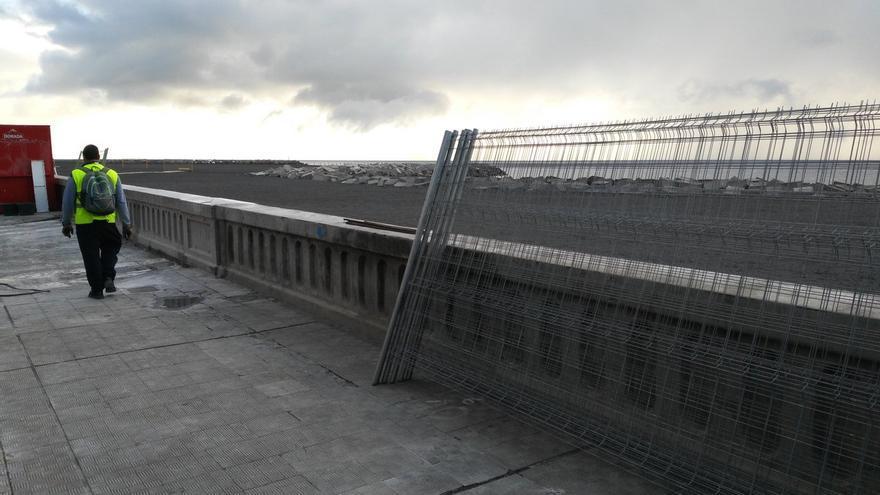 Trabajadores del Ayuntamiento de Santa Cruz de La Palma proceden este lunes a retirar las vallas metálicas que fueron colocadas a lo largo del muro de la Avenida Marítima para cerrar el  acceso a la playa durante los carnales.