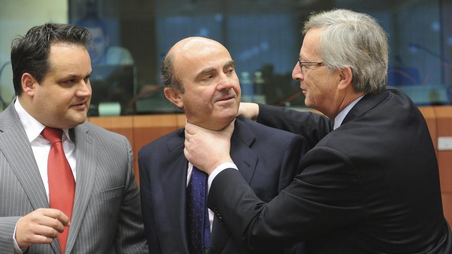 Jean-Claude Juncker bromea con Luis de Guindos al comienzo de una reunión del Eurogrupo en marzo de 2012