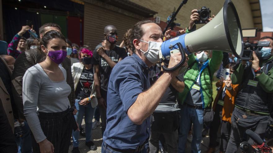 La ministra de Igualdad y el candidato de Unidas Podemos a la Presidencia de la Comunidad, Pablo Iglesias con un megáfono se dirige al público durante un acto del partido en el Polideportivo municipal Cerro Buenavista de Getafe,  a 27 de abril de 2021, en