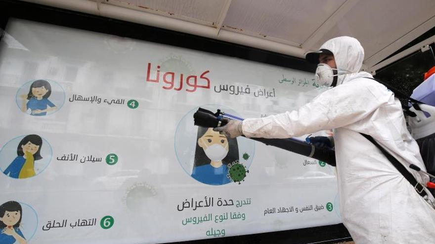 Un operario desinfecta una parada de autobús en Argel.