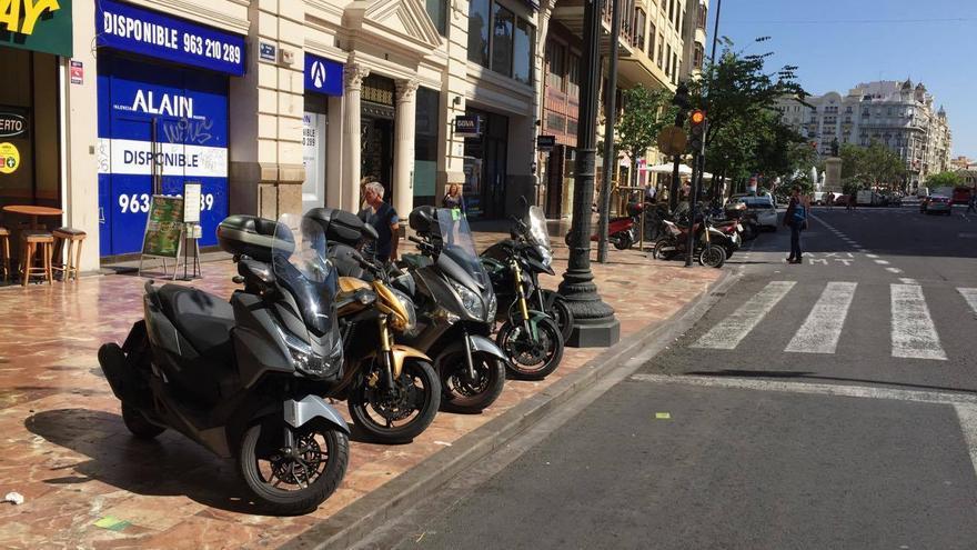 Varias motos aparcadas en una acera ante la falta de espacio en la zona habilitada al fondo