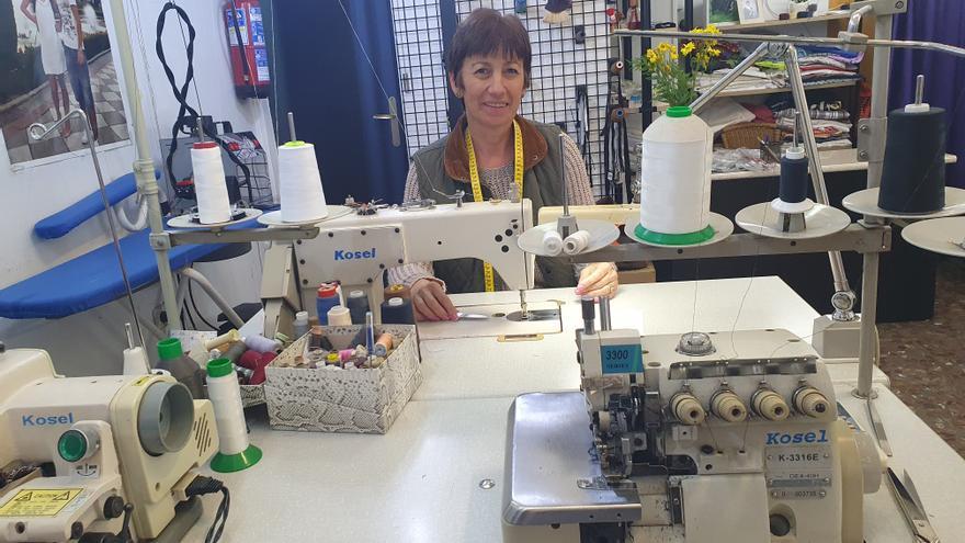 La modista Lissa, detrás de la máquina de coser en su taller.