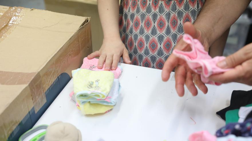 Archivo - Una mujer embarazada revisa ropa de bebé