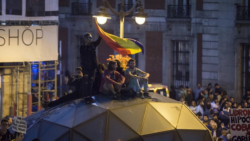 """Manifestantes se encaraman a la cúpula de entrada y salida al Metro de Sol, al finalizar la manifestación """"rodea el Congreso"""""""