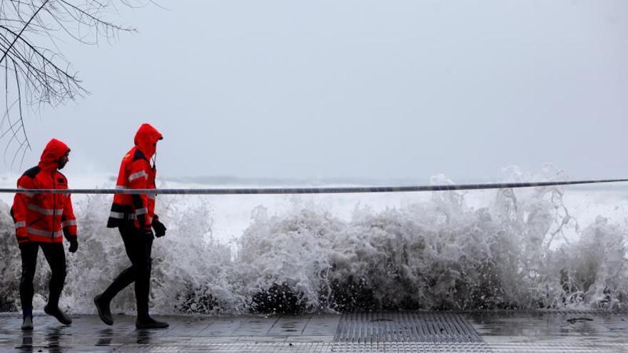 Una ola supera el paseo marítimo de la provincia gallega de A Coruña este jueves ante la presencia de dos bomberos. Las provincias de A Coruña y Pontevedra están en alerta roja por olas de hasta diez metros y fuertes vientos, mientras que en la montaña de Lugo y Ourense las posibles acumulaciones de nieve de unos 20 centímetros activan la alerta naranja, razón por la que se han suspendidos las clases en esta zona.
