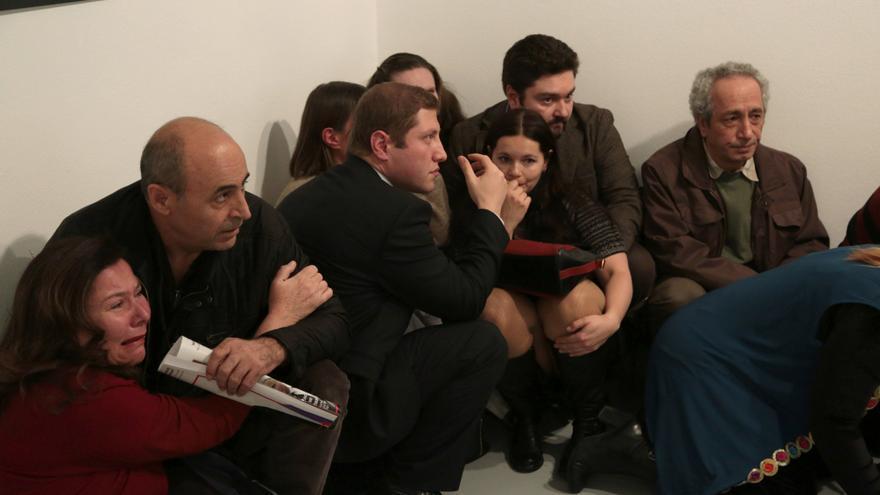 Un grupo de personas se refugia en la galería donde se produce el atentado (Associated Press)