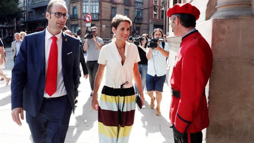 María Chivite, acompañada del socialista Jorge Aguirre, saluda a la Policía Foral al entrar al Parlamento.