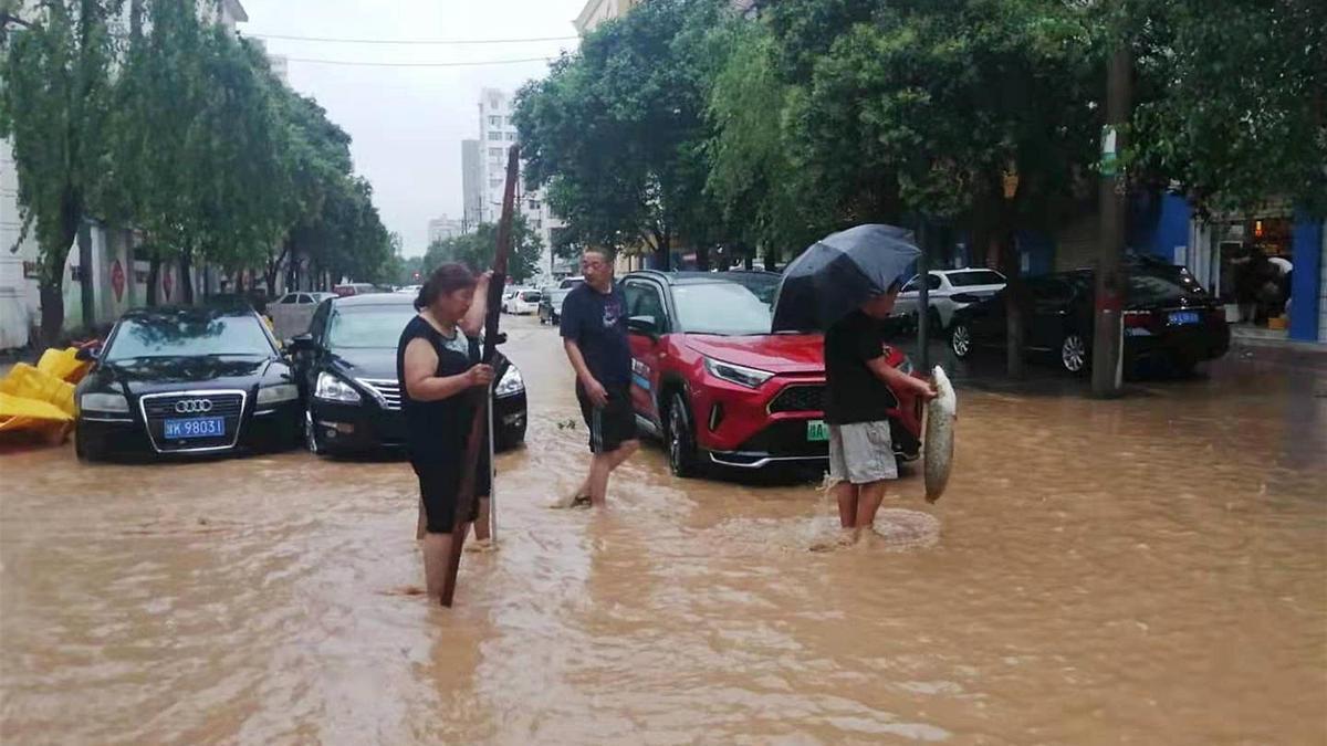 Gente caminando en las calles inundadas de Zhengzhou, China.