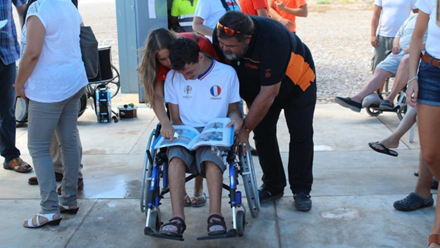 Voluntarios de Protección Civil ayudan a un usuario en la playa accesible de Almardà