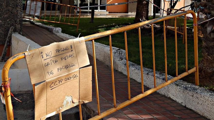 Un cartel informa sobre desprendimientos en la fachada de uno de los edificios de La Cornisa. (CA).