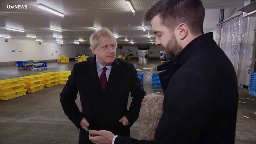 Boris Johnson mientras es entrevistado por un reportero que le muestra la foto de un niño enfermo
