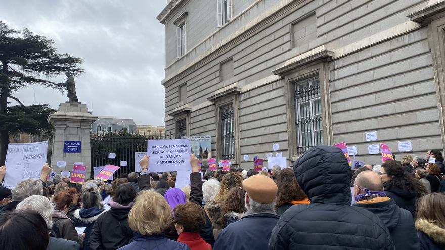 Asistentes a la concentración en Madrid por la igualdad en la Iglesia alzan sus pancartas.