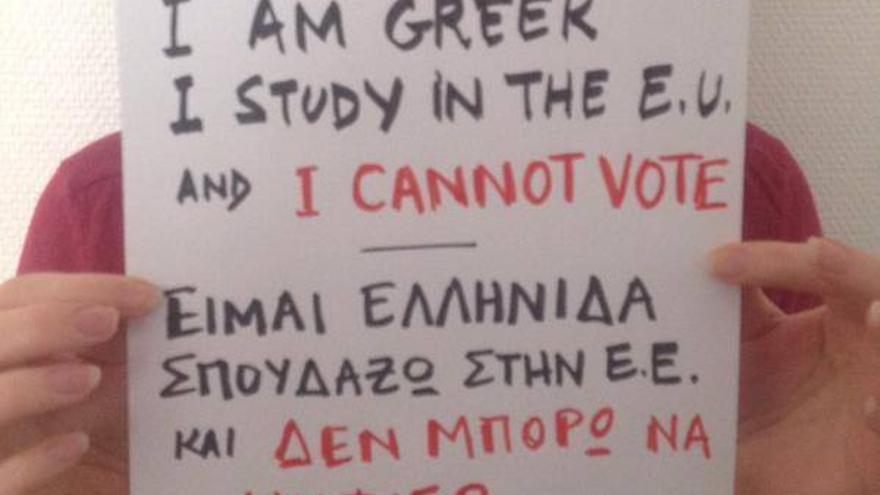 """Una joven sostiene un cartel que dice: """"Soy griega, estudio en la Unión Europea y no puedo votar""""."""
