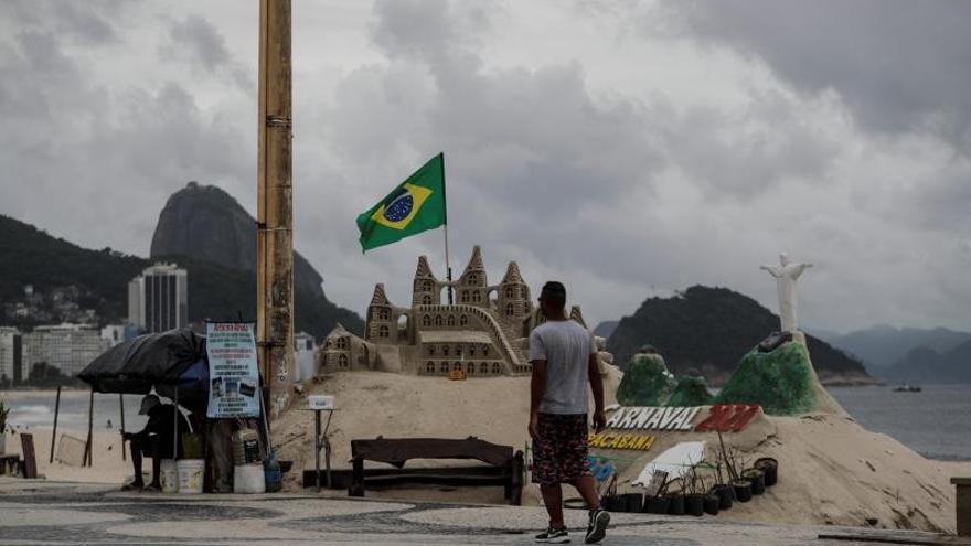Un hombre camina en la calzada de la playa de Copacabana este sábado en Río de Janeiro (Brasil). El número de casos de coronavirus en Brasil llegó a 1.000 y el de muertos por la enfermedad a doce, según los datos registrados al mediodía de este sábado por las secretarías regionales de salud en el país más poblado y más afectado por la pandemia en América Latina.