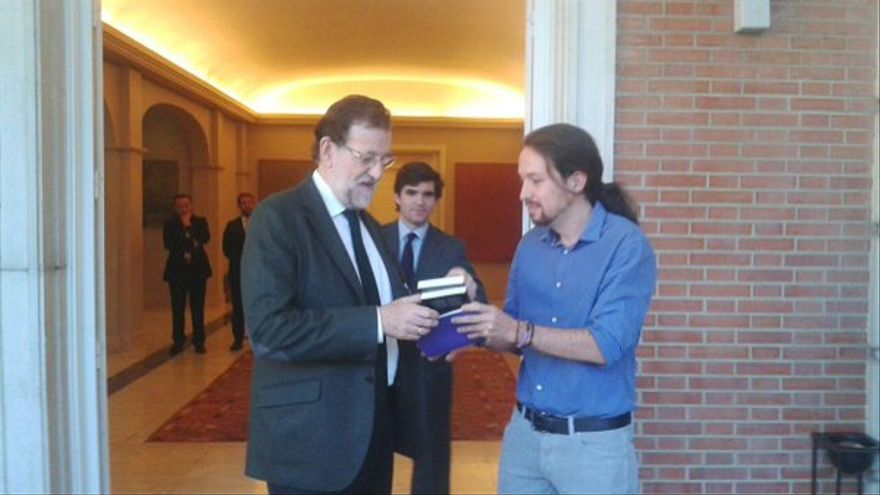 El secretario general de Podemos, Pablo Iglesias, entrega un ejemplar de Juan de Mairena, de Antonio Machado, al presidente del Gobierno, Mariano Rajoy. / Podemos