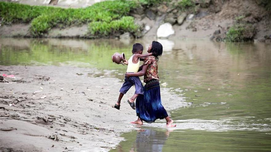 """Dos hermanos de la minoría musulmana rohingya cruzan un pequeño canal en un campamento improvisado """"en tierra de nadie"""", en el área fronteriza entre Birmania y Bangladesh."""