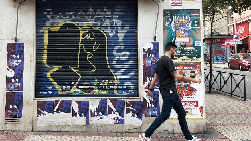 """Un vecino de Usera pasa delante de una pared empapelada con afiches con la inscripción """"No contéis conmigo""""."""