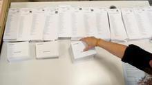 Una persona coloca las listas con las diferentes candidaturas que concurren a las elecciones generales que se celebran mañana durante el montaje del colegio electoral en el CEIP Pi i Margall de Madrid.